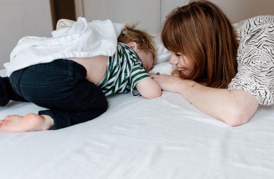 moeder met zoon in bed aan het spelen
