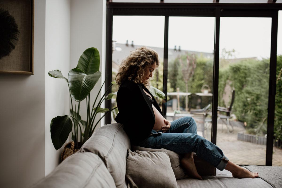 zwangere vrouw poseert op bank in woonkamer