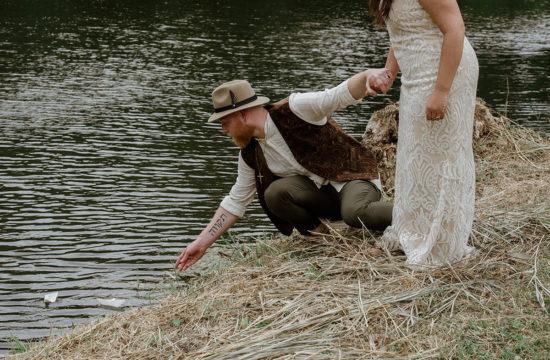 boho bruidspaar hand in hand zet wensboot in water
